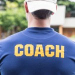 back of a sport coach's blue shirt with the yellow Coach word written on it
